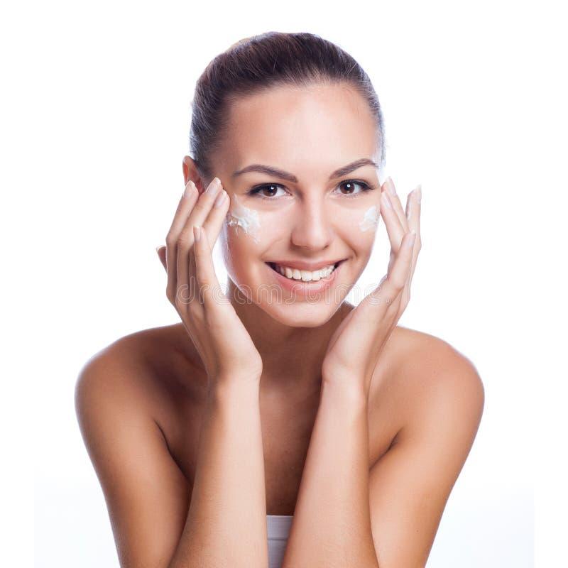 Mooi model die kosmetische roombehandeling toepassen stock afbeeldingen