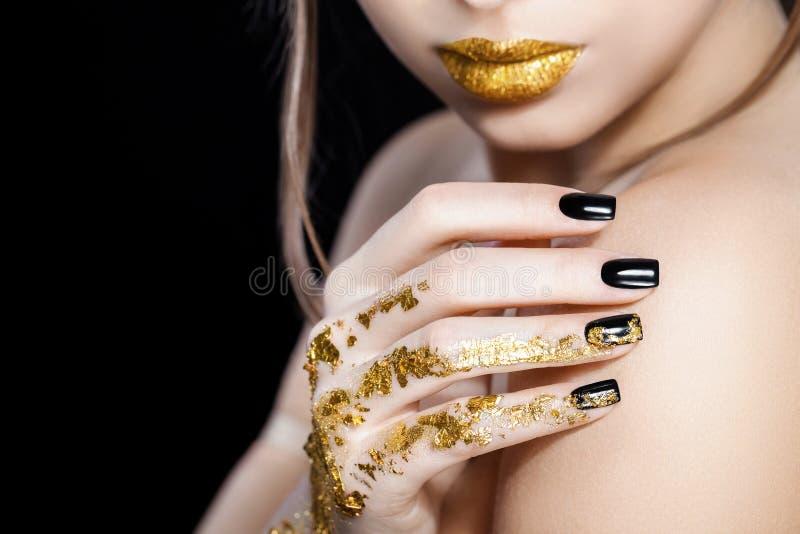 Mooi model het gezichtsportret van de Maniervrouw met gouden lippenstift en zwarte spijkers Glamourmeisje met heldere make-up sch stock afbeelding