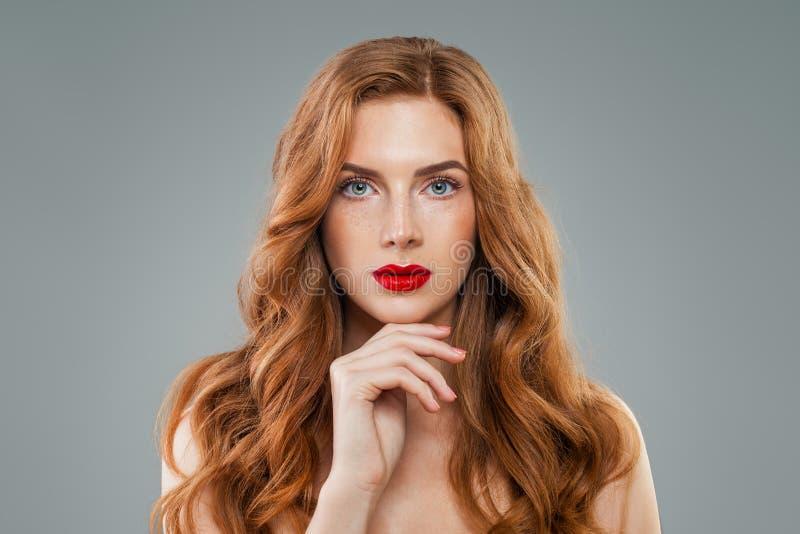 Mooi model met lang krullend rood haar die camera bekijken Golvend glanzend haar, perfect gezicht royalty-vrije stock foto's