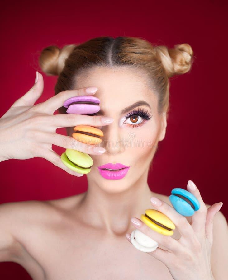 Mooi model met make-up en creatief kapsel die kleurrijke makarons, studiospruit op rode achtergrond houden royalty-vrije stock fotografie