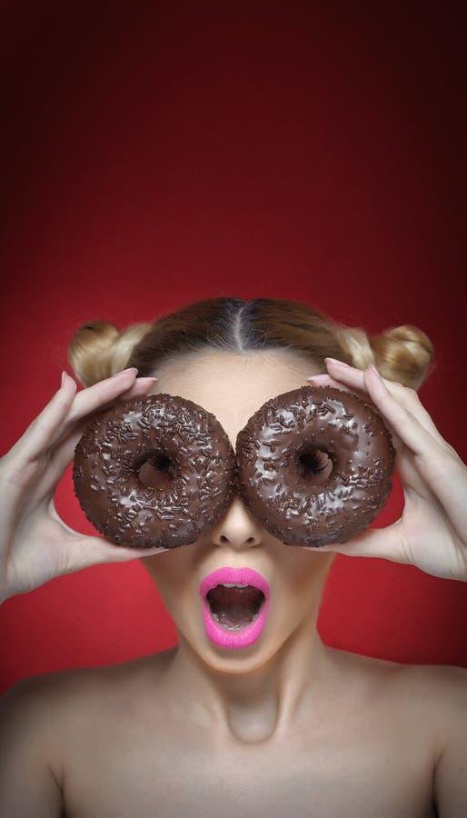 Mooi modelmeisje die met heldere roze lippenstift chocolade twee houden donuts Grappige blije vrouw met snoepjes op donkerrode ac stock afbeeldingen