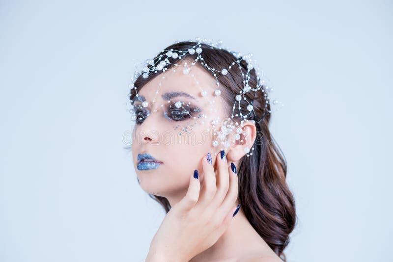 Mooi modelmeisje met het blauwe ontwerp, het gezicht en het haar van de manicurespijker met parels, bergkristallen, decoratie De  royalty-vrije stock afbeelding