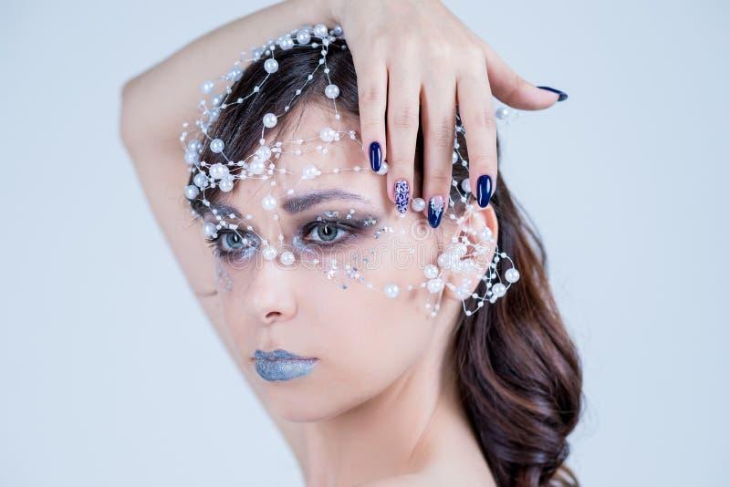 Mooi modelmeisje met het blauwe ontwerp, het gezicht en het haar van de manicurespijker met parels, bergkristallen, decoratie De  royalty-vrije stock foto's