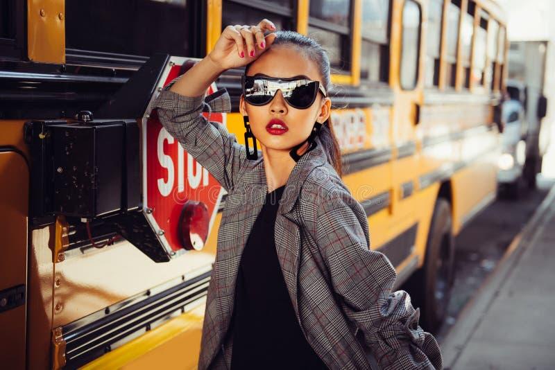 Mooi modieus Aziatisch modelmeisje die modieuze zwarte zonnebril dragen die in openlucht op stadsstraat dichtbij bus stellen royalty-vrije stock fotografie