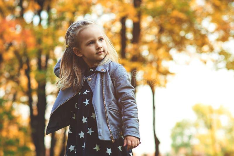 Mooi modieus babymeisje die in de herfstpark lopen Het gelukkige kind spelen in openlucht in de herfst Het modieuze meisje geniet stock afbeelding