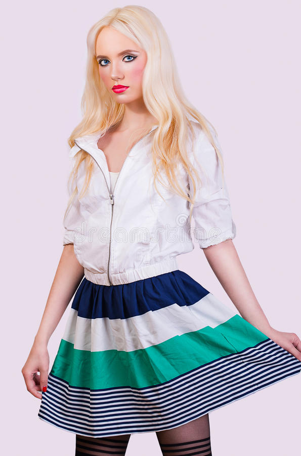 Mooi modieus blondemeisje in rok met strepen stock fotografie