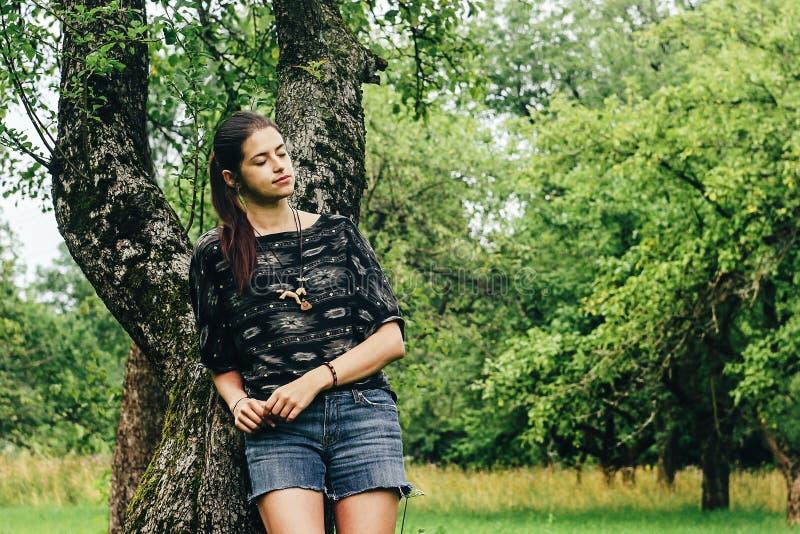 Mooi modieus hipstermeisje die zich bij oude appelboom bevinden in geep stock fotografie