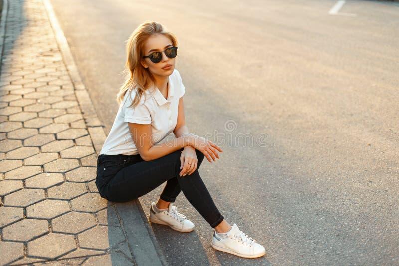 Mooi modieus jong blond meisje in zwarte glazen in een wit stock afbeeldingen