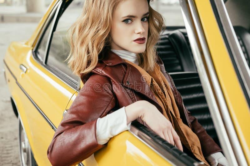 mooi modieus meisje in de zitting van het leerjasje in ouderwetse auto en het kijken stock foto