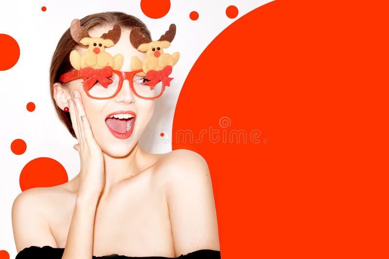 Mooi modieus meisje die in zwarte uitrusting nieuw jaar vieren Meisje in grappige glazen met de herten en de bogen van het nieuwe royalty-vrije stock afbeeldingen