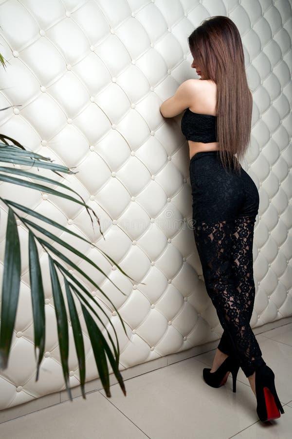 Mooi modieus meisje in een zwarte kostuumtribunes bij diamant-sha royalty-vrije stock afbeelding