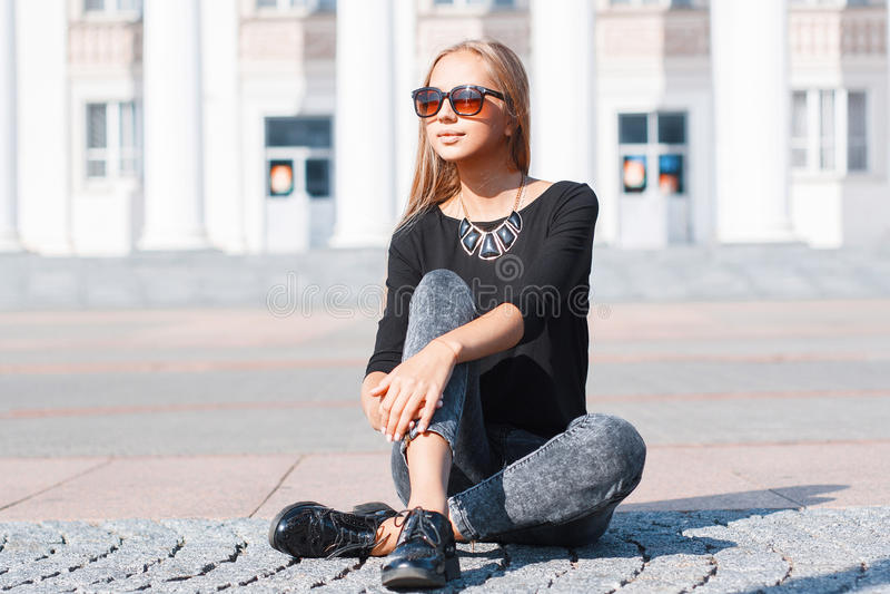Mooi modieus meisje in een zwarte T-shirt, jeans en schoenensitti stock fotografie