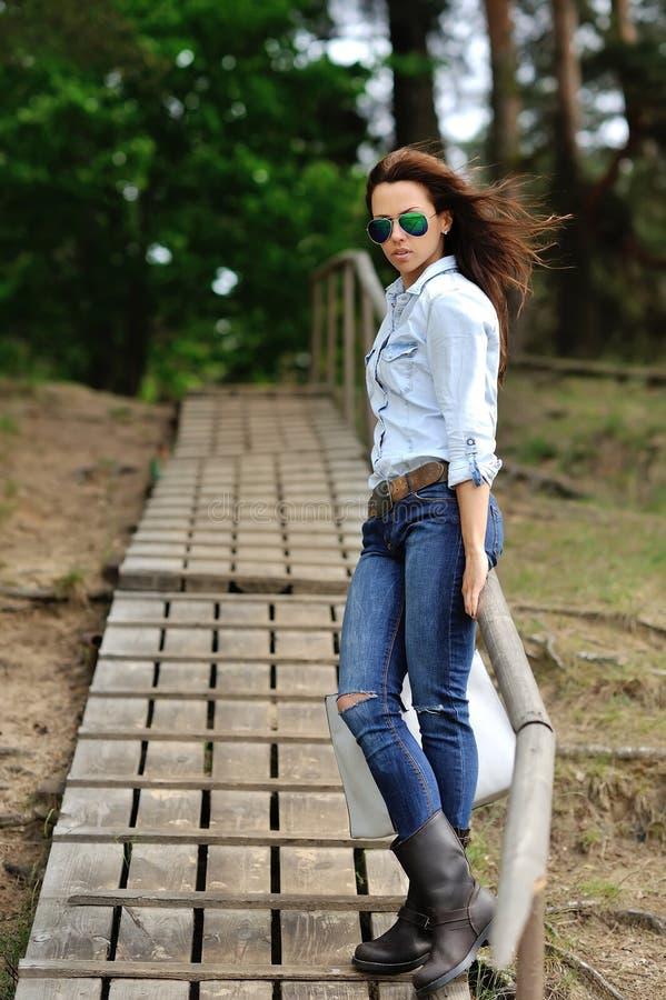 Mooi modieus meisje in jeansoverhemd en zonnebril - volledige leng royalty-vrije stock afbeeldingen