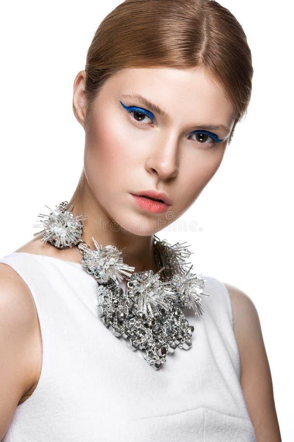 Mooi modieus meisje met de blauwe pijlen op ogen, vlot haar en originele decoratie rond haar hals Model in wit beau royalty-vrije stock foto's