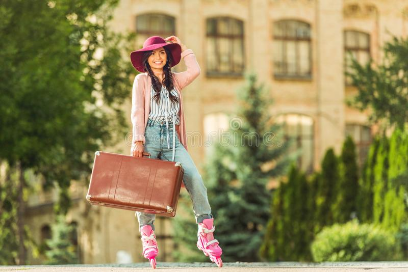 mooi modieus meisje in rolschaatsen die koffer houden en bij camera glimlachen royalty-vrije stock afbeeldingen
