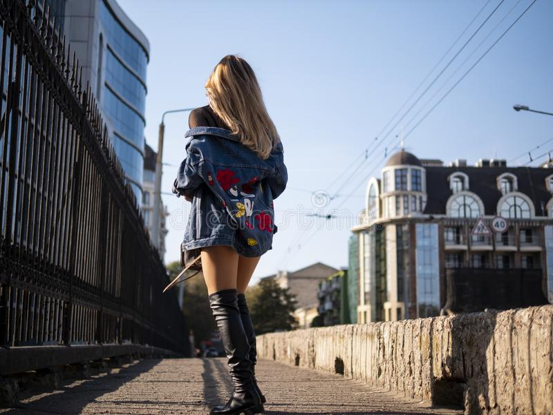 Mooi modieus tienermeisje met stromend haar in de volledige groei op een stadsbrug stock foto's