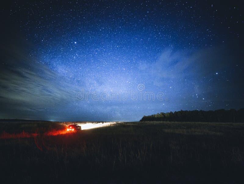 Mooi nachtlandschap met auto en sterren stock afbeelding