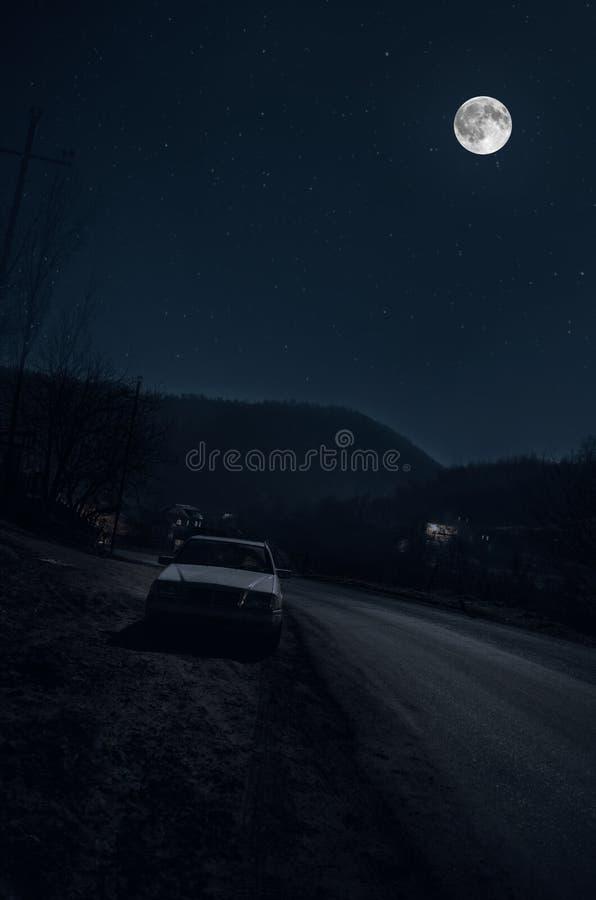 Mooi nachtlandschap van grote volle maan die over de bergweg met heuvel en bomen, met auto dichtbij weg toenemen royalty-vrije stock afbeelding