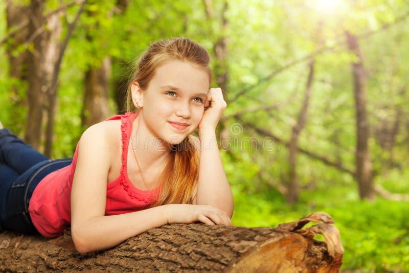 Mooi nadenkend meisje die op het logboek leggen stock fotografie