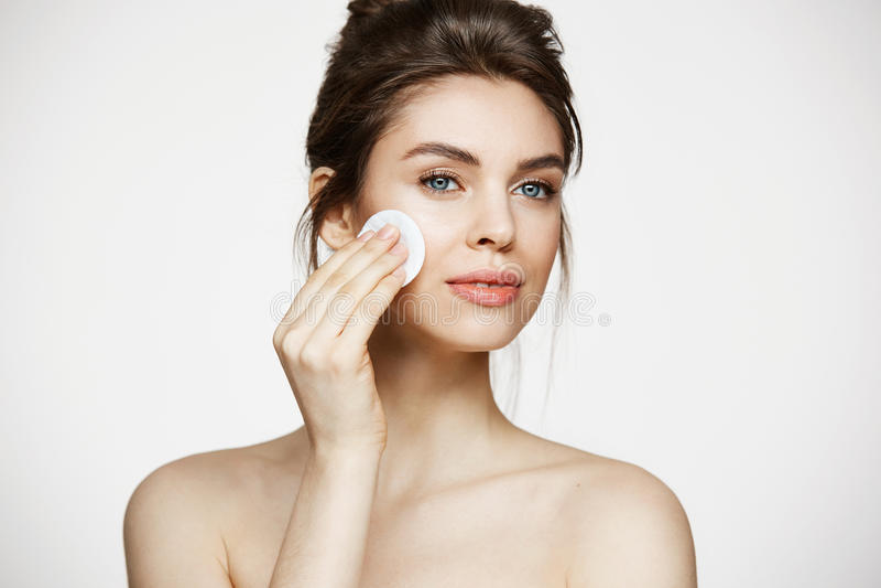 Mooi natuurlijk donkerbruin meisjes schoonmakend gezicht met katoenen spons die over witte achtergrond glimlachen De kosmetiek en royalty-vrije stock foto's