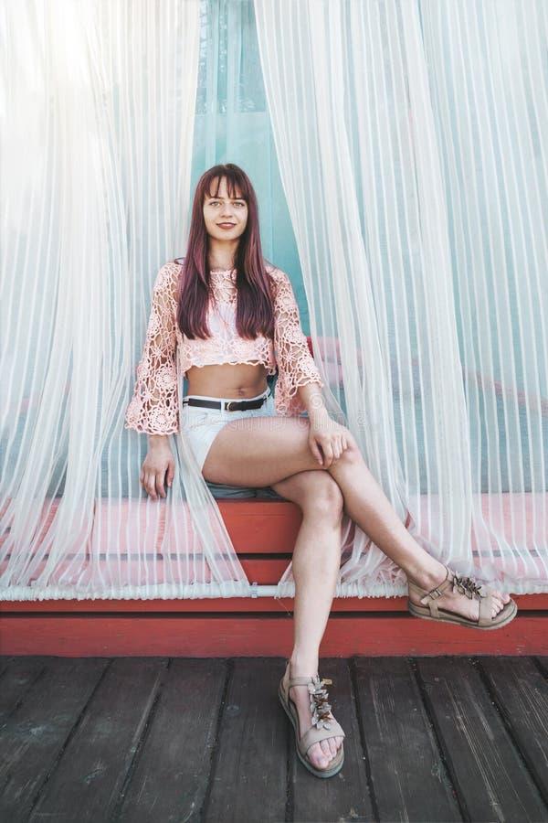 Mooi onbezorgd sexy meisje door wit gordijn bij de toevlucht van de strandzitkamer, ligstoelen De vakantievakantie van de de zome royalty-vrije stock fotografie