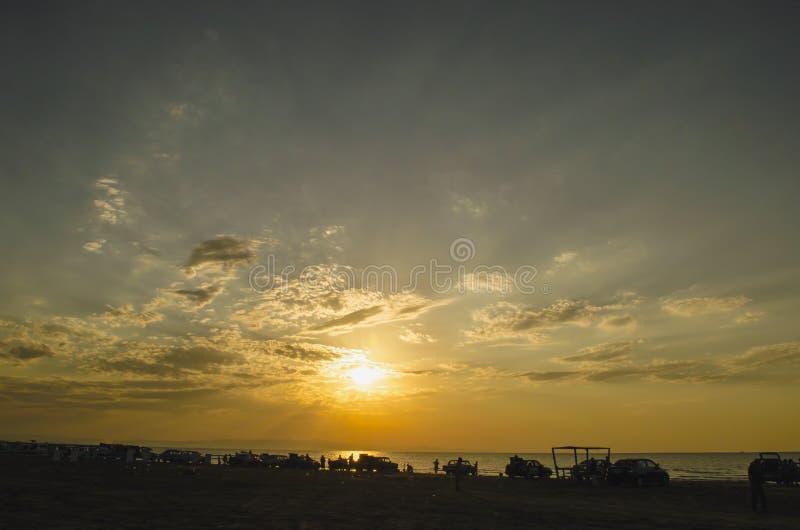 Mooi opvlammend zonsonderganglandschap bij Kaspische overzees en oranje hemel boven het met ontzagwekkende zon gouden bezinning o stock fotografie