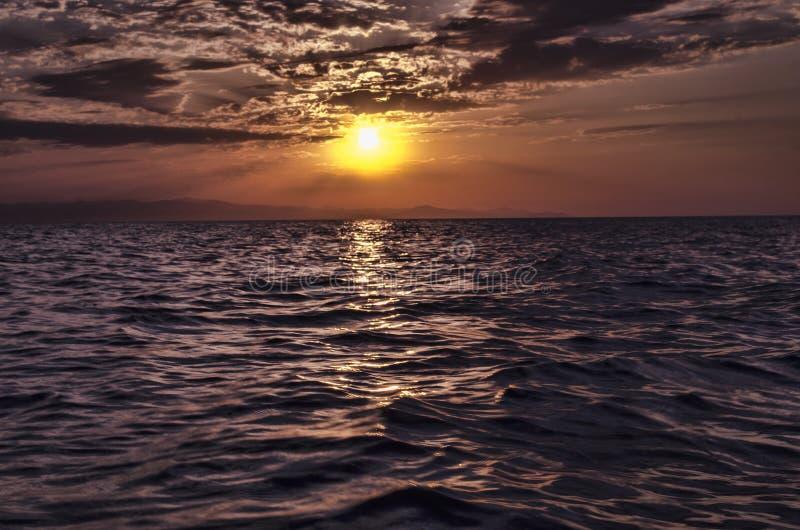 Mooi opvlammend zonsonderganglandschap bij Kaspische overzees en oranje hemel boven het met ontzagwekkende zon gouden bezinning o stock foto