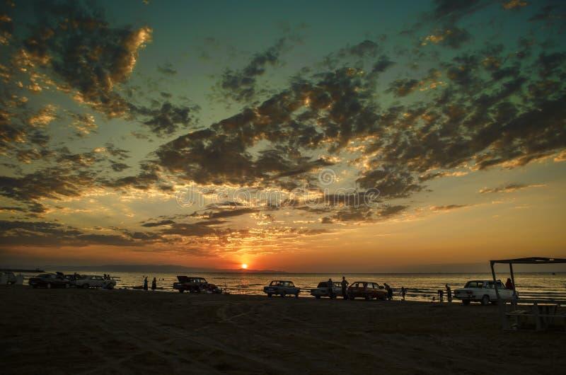 Mooi opvlammend zonsonderganglandschap bij Kaspische overzees en oranje hemel boven het met ontzagwekkende zon gouden bezinning o royalty-vrije stock foto's