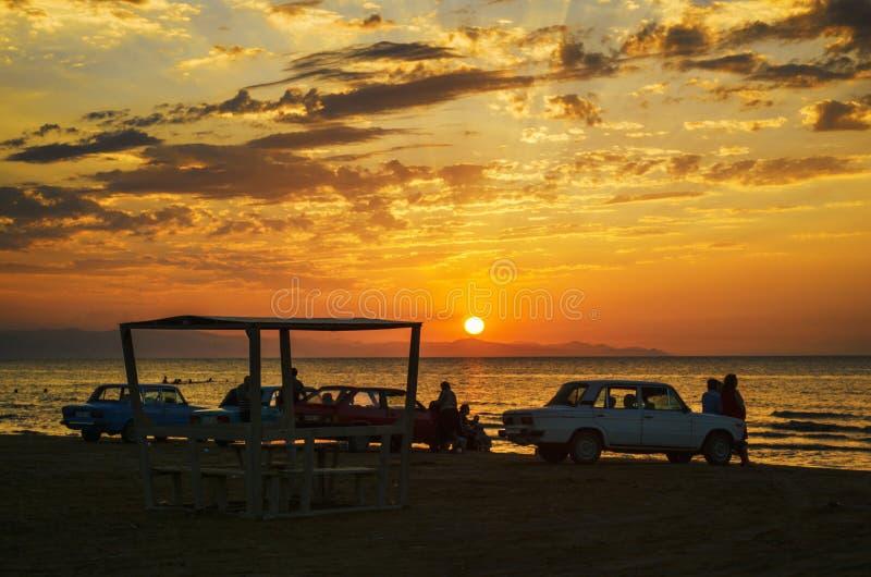 Mooi opvlammend zonsonderganglandschap bij Kaspische overzees en oranje hemel boven het met ontzagwekkende zon gouden bezinning o stock afbeelding