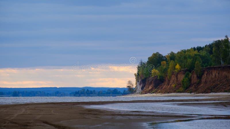 Mooi oranje en rood de herfstbos, heel wat bomen op een klip dichtbij de rivier Autumn Landscape stock foto