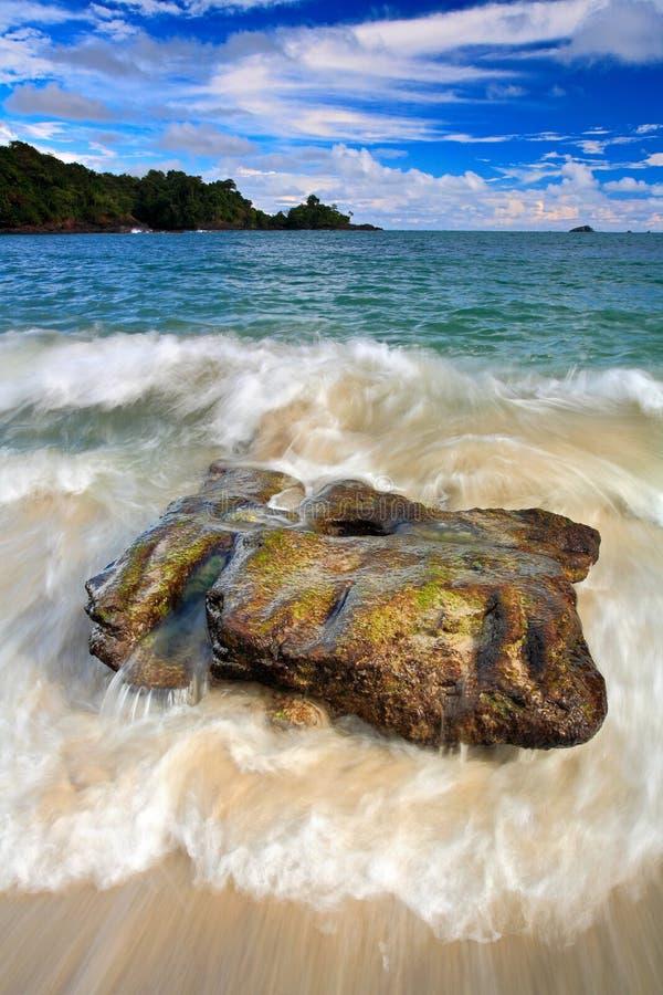 Mooi overzees kustlandschap met golven en steen Groen eiland op de achtergrond Grote steen in het water Oceaan met donkerblauw s stock foto's