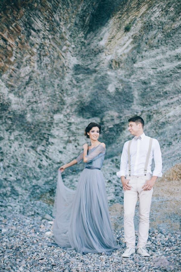 Mooi paar dichtbij de rotsen, die met een glimlach elkaar bekijken stock fotografie