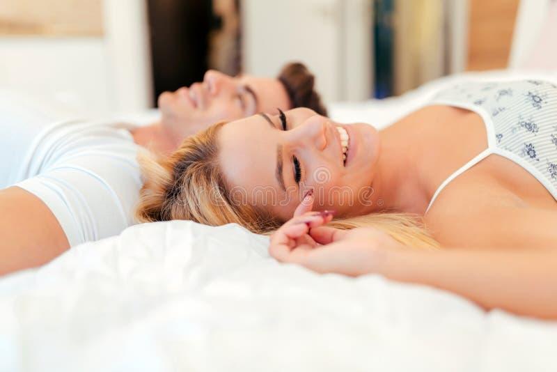 Mooi paar die bij bed en het glimlachen liggen royalty-vrije stock foto