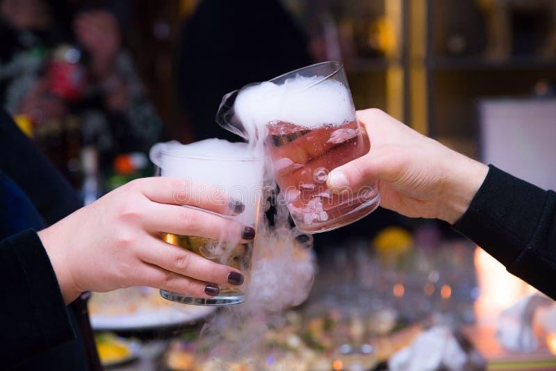 Mooi paar die droge ijscocktails houden bij de partij Purpere cocktaildrank met ijsdamp bij de club, viering stock fotografie