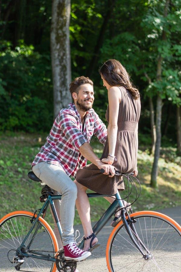 Mooi paar die een stadsfiets berijden en aan elkaar glimlachen stock afbeeldingen