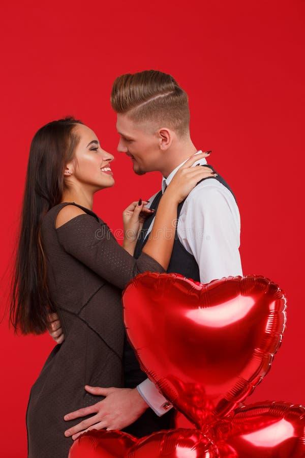 Mooi paar die en elkaar op een rode achtergrond kussen koesteren Het concept de Dag van Valentine ` s stock foto