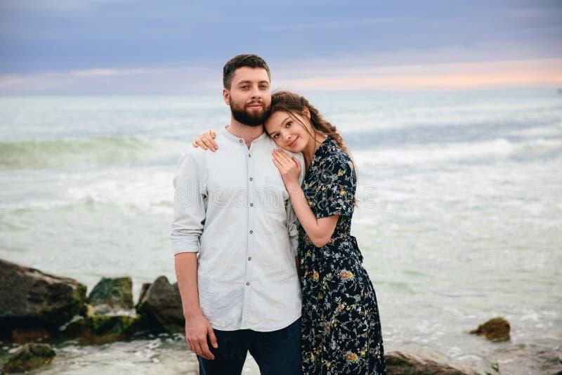 Mooi paar die in liefde op het strand koesteren Status op het strand op de overzeese achtergrond royalty-vrije stock foto's