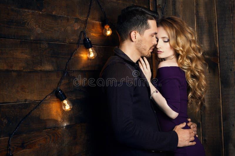 Mooi paar die in liefde tegen de achtergrond van glowi koesteren royalty-vrije stock afbeeldingen