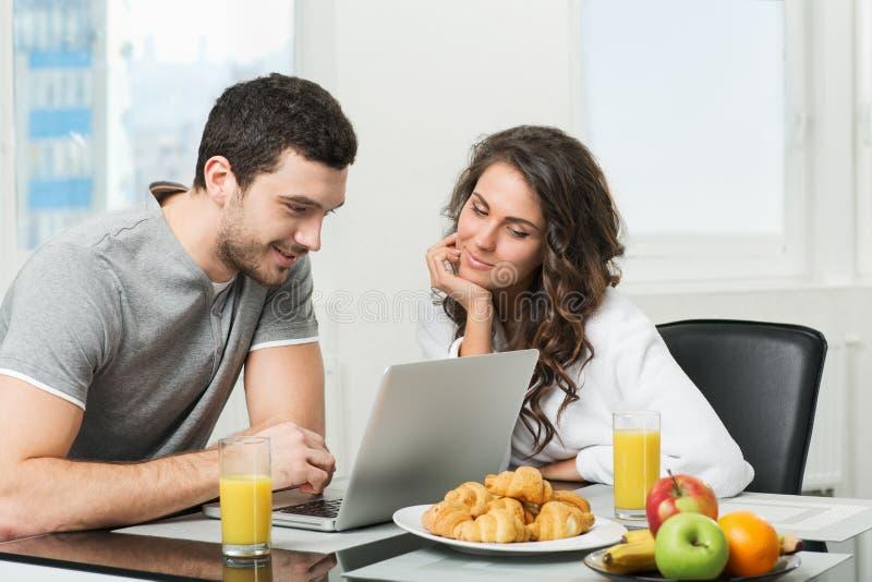 Mooi paar die ontbijt met laptop hebben royalty-vrije stock foto's