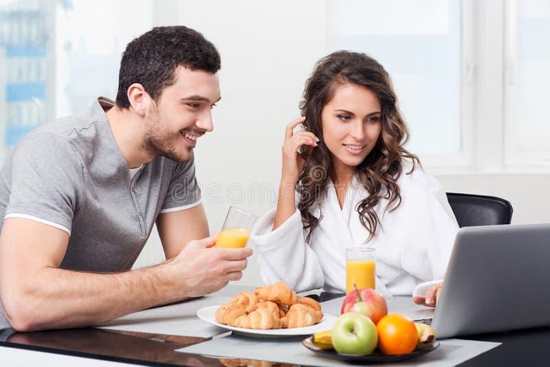 Mooi paar die ontbijt met laptop hebben stock afbeelding