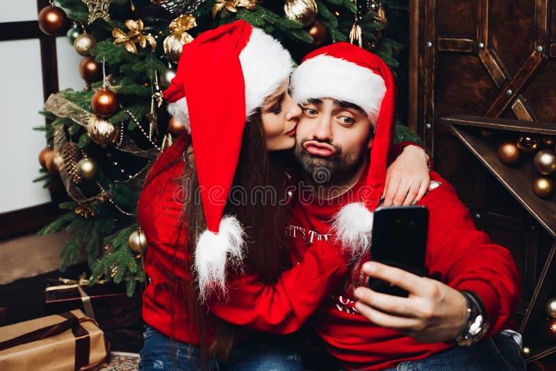 Mooi paar die in santahoeden selfie op mobiele telefoon maken royalty-vrije stock foto's