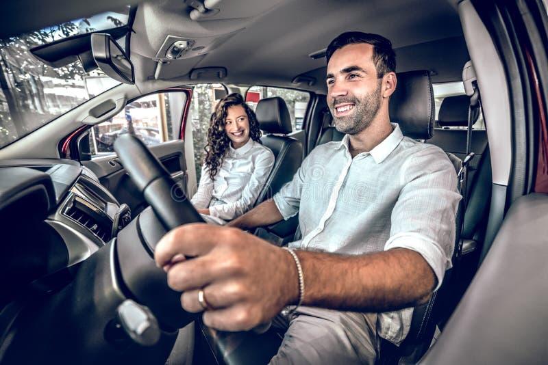 Mooi paar die terwijl het zitten in hun nieuwe auto glimlachen stock fotografie