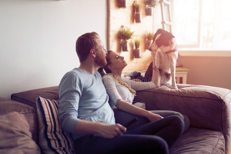 Mooi paar die thuis en van hun hond ontspannen houden royalty-vrije stock afbeeldingen