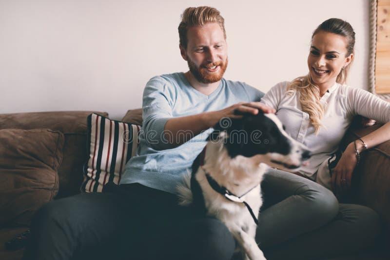 Mooi paar die thuis en van hun hond ontspannen houden royalty-vrije stock fotografie
