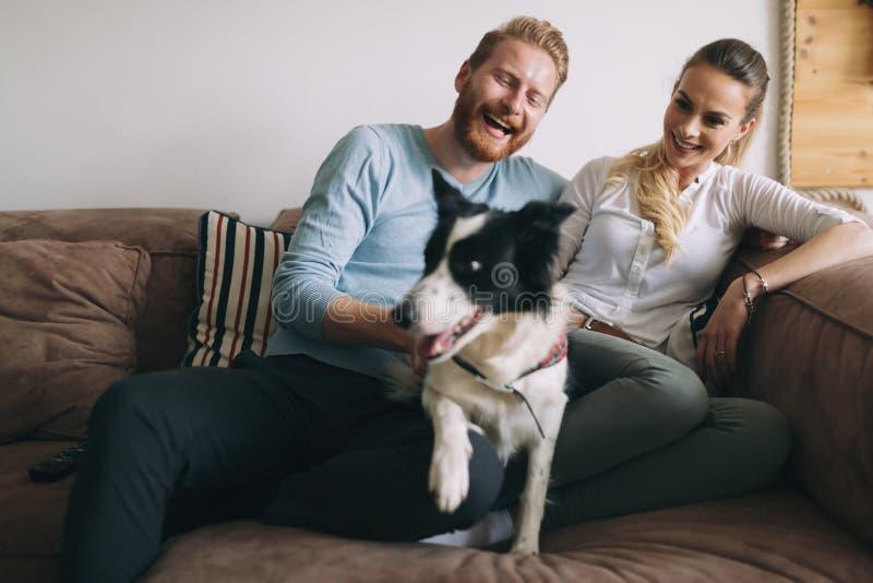 Mooi paar die thuis en van hun hond ontspannen houden stock afbeelding