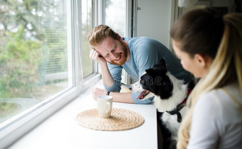 Mooi paar die thuis en van hun hond ontspannen houden stock foto