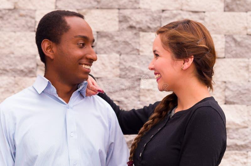 Mooi paar die tussen verschillende rassen en voor camera, haar hand op zijn schouder stellen glimlachen die elke anderen onderzoe royalty-vrije stock afbeeldingen