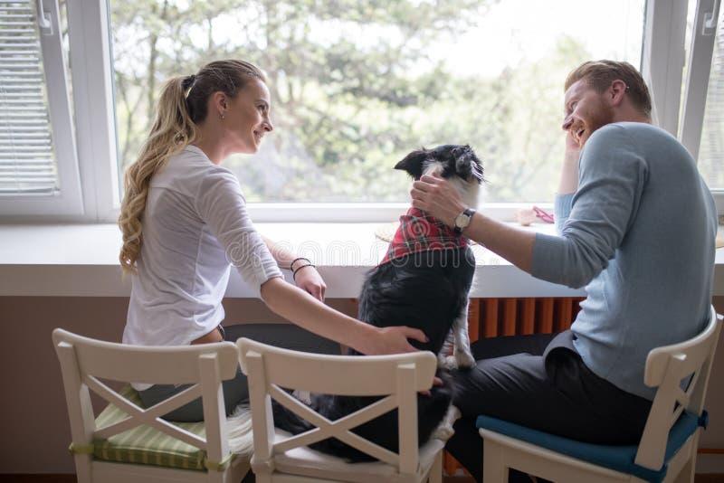 Mooi paar die van metgezel van hun hond thuis genieten stock foto's