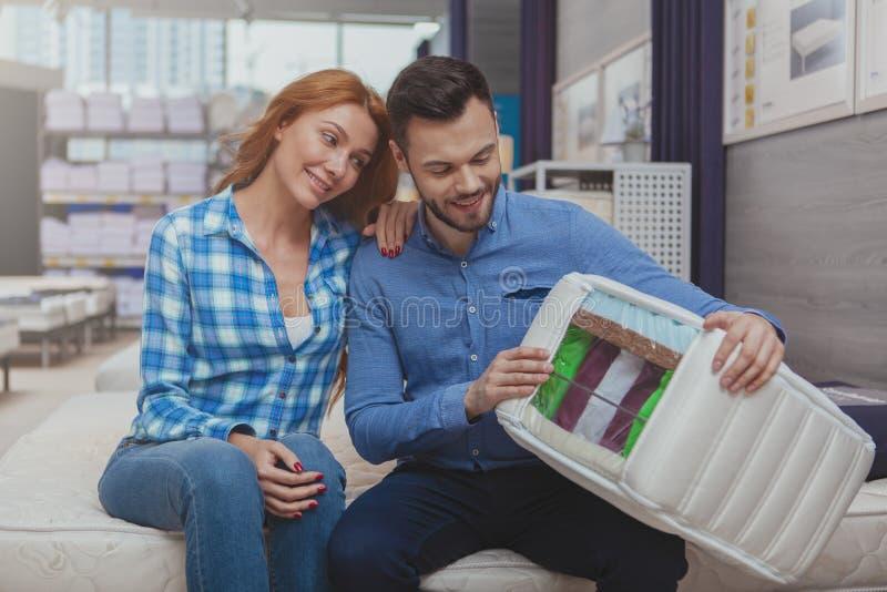 Mooi paar die voor nieuwe matras bij meubilairopslag winkelen royalty-vrije stock foto