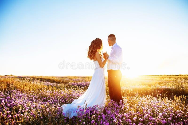 Mooi paar in gebied, Minnaars of jonggehuwde het stellen op zonsondergang met perfecte hemel stock afbeeldingen